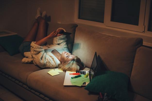 Estudante caucasiana cansada conversando no telefone enquanto está sentada no sofá depois de fazer a lição de casa tarde da noite