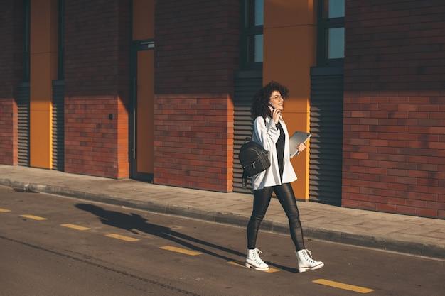 Estudante caucasiana com cabelo encaracolado andando do lado de fora com uma bolsa e um laptop enquanto fala ao telefone