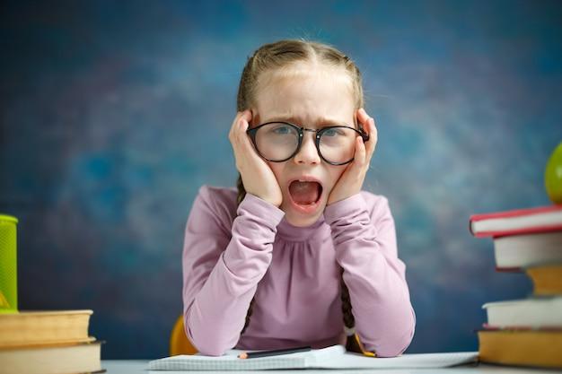 Estudante caucasiana pequena garota gritar estudo foto