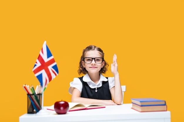 Estudante caucasiana sorridente levantando a mão sentada na mesa, aula de inglês, bandeira da grã-bretanha