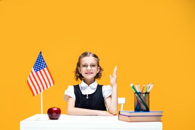 Estudante caucasiana sorridente levantando a mão, sentada na mesa durante a aula, aula de inglês, bandeira dos eua