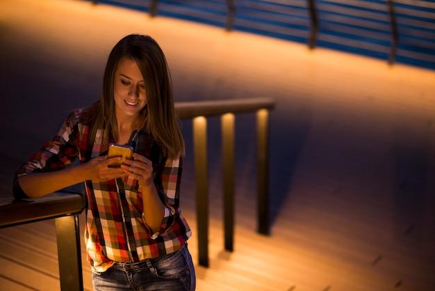 Estudante caucasiano feminino lendo mensagens de texto em celular com reflexo na tela do rosto, telefone com tela em branco