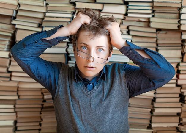 Estudante chocado mantém as mãos no cabelo sobre livros