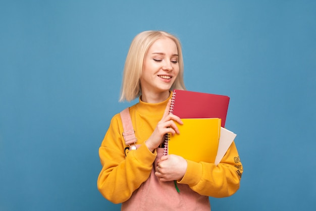 Estudante com cabelo claro e roupas casuais está de pé no azul, segura um caderno na mão e sorri