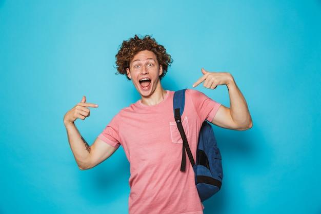 Estudante com cabelos cacheados, vestindo roupas casuais e mochila, apontando os dedos para si mesmo