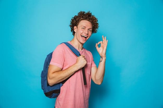 Estudante com cabelos cacheados, vestindo roupas casuais e mochila sorrindo e mostrando sinal ok
