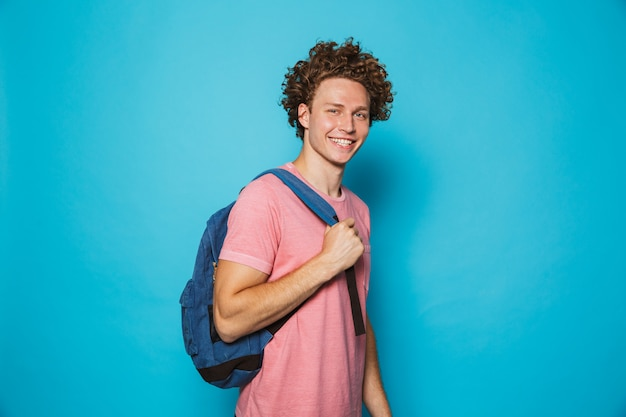 Estudante com cabelos cacheados, vestindo roupas casuais e mochila, sorrindo para a câmera