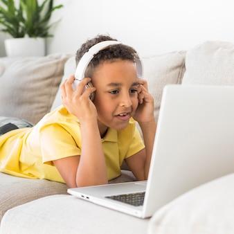 Estudante com fones de ouvido, olhando para laptop
