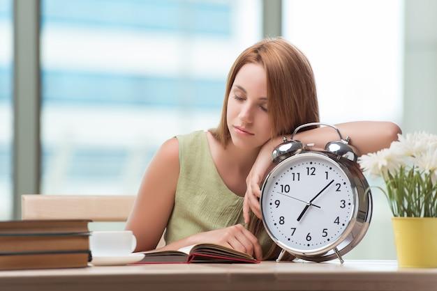 Estudante com gian despertador, preparando-se para os exames