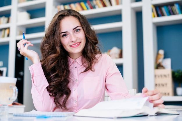 Estudante com livro e caneta na biblioteca