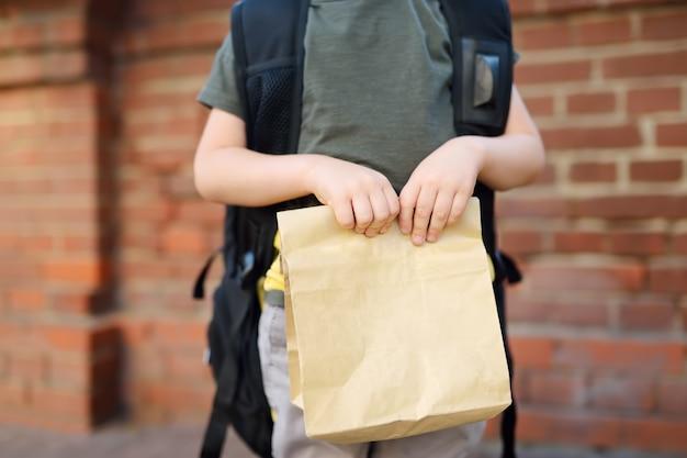 Estudante com mochila grande e lancheira perto do prédio da escola.