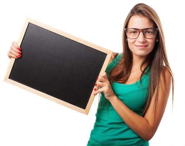 Estudante com vidros segurando um quadro-negro