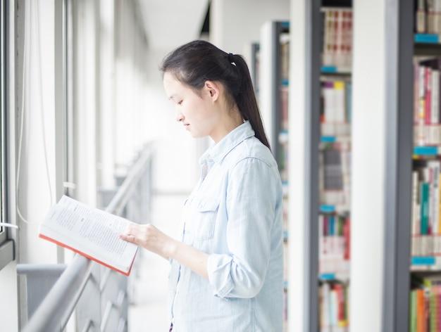 Estudante concentrada que lê um livro com estantes de fundo