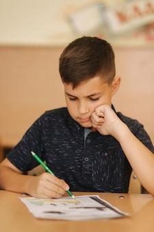 Estudante concentrado sentado à mesa e escrevendo no livro de exercícios. conceito de aprendizagem