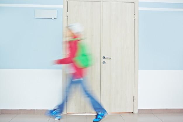 Estudante correndo através de corredor