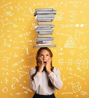Estudante criança preocupada devido ao excesso de livros para ler e estudar