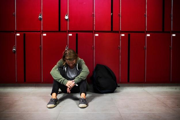Estudante curvando a cabeça e sentado no chão