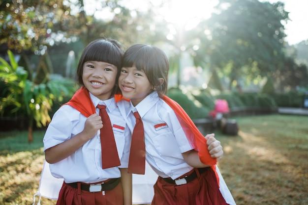 Estudante da escola indonésia segurando bandeira durante o dia da independência