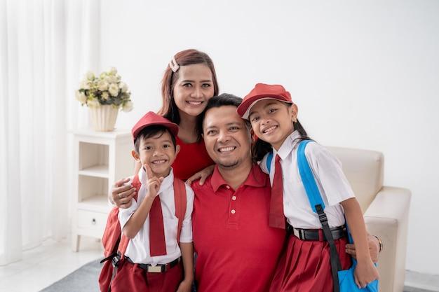 Estudante da escola primária indonésio com os pais sorrindo