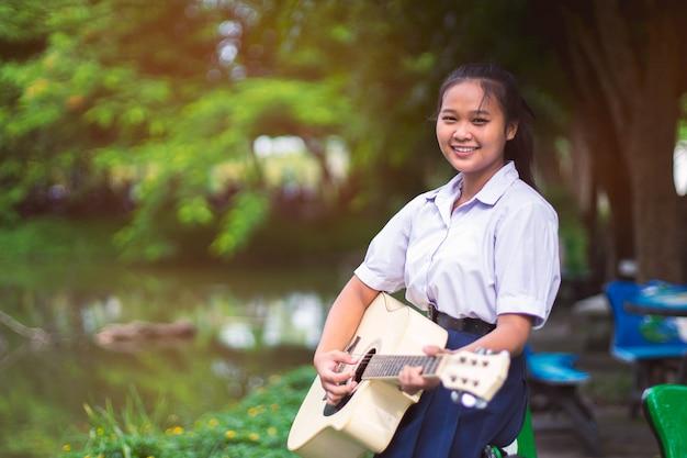 Estudante da menina do sorriso que guarda e que joga a guitarra.