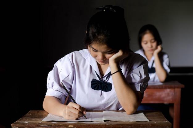 Estudante da menina que lê e que escreve o exame com esforço. estilo chave baixo.