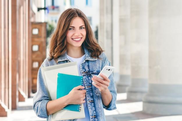 Estudante da moça que sorri contra a universidade. linda garota estudante detém pastas, cadernos e celular nas mãos. aprendizagem, educação