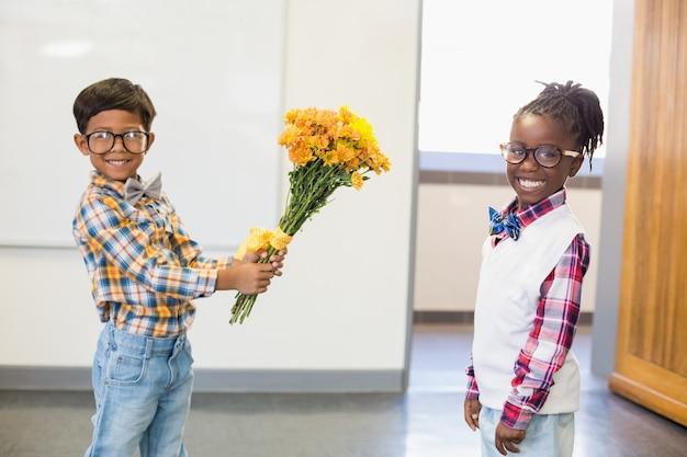 Estudante dando um ramo de flores para uma colegial