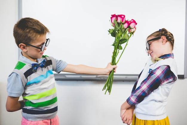 Estudante dando um ramo de flores para uma garota na sala de aula