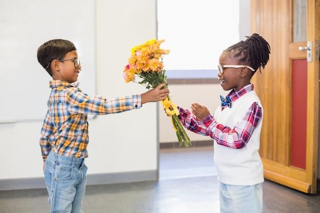 Estudante dando um ramo de flores para uma menina