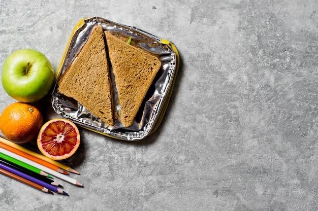 Estudante de almoço em um recipiente. sanduíche, maçã, laranja.