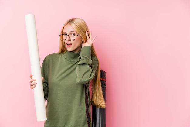 Estudante de arquitetura loira jovem tentando ouvir uma fofoca.