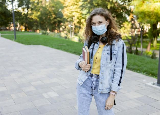 Estudante de cabelo encaracolado em máscara médica facial, segurando uma pilha de livros ao ar livre. educação durante uma pandemia