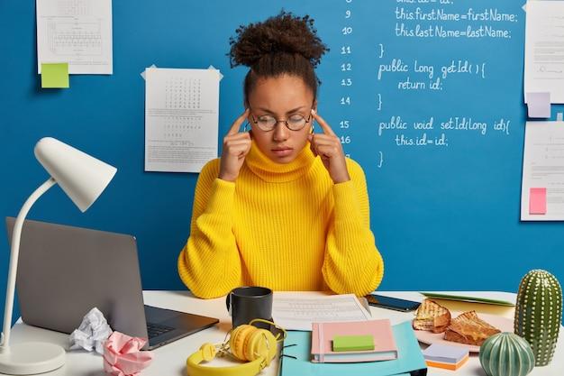 Estudante de cabelo encaracolado mantém os dois dedos nas têmporas, tenta reunir seus pensamentos, relembra informações em mente