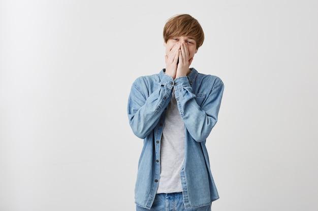 Estudante de cabelos loiros, vestido com camisa jeans azul, cobrindo o rosto com as mãos, olhando com olhar perplexo, cansado de trabalho estressante, preocupado com o exame importante na universidade