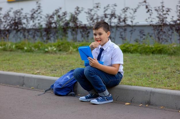 Estudante de camisa branca com gravata azul, segura uma lancheira azul e come um pedaço de maçã