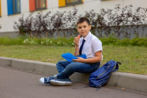 Estudante de camisa branca com gravata azul, segura uma lancheira azul e uma fatia de maçã, olha para a câmera