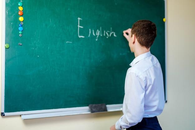 Estudante de camisa leve escrevendo palavras em inglês no quadro-negro. de volta ao conceito de escola.