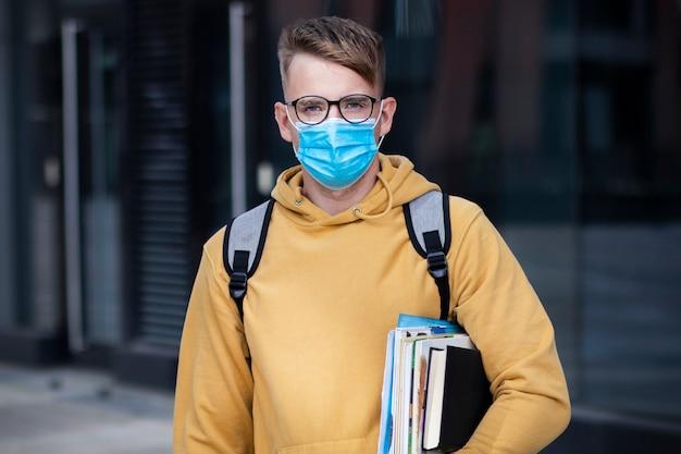 Estudante de cara, rapaz aluno, jovem em máscara médica protetora e óculos na universidade de ar livre de rosto com livros