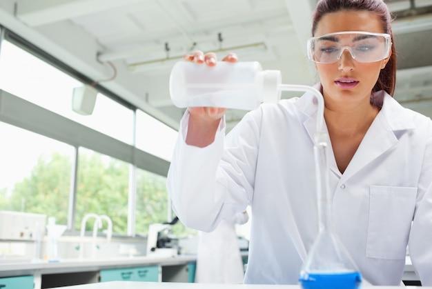 Estudante de ciência feminina vazando líquido