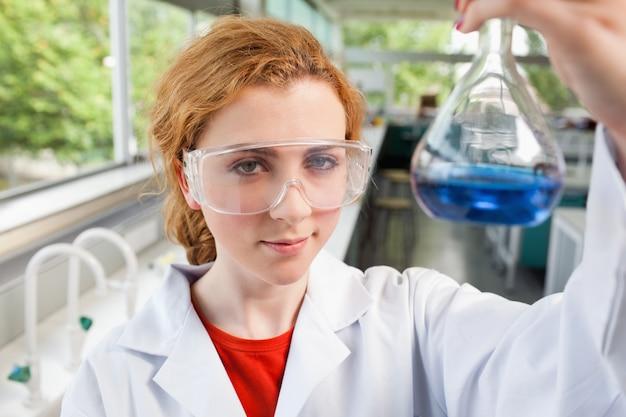 Estudante de ciência que segura um frasco