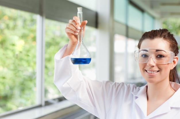Estudante de ciências femininas segurando um líquido azul