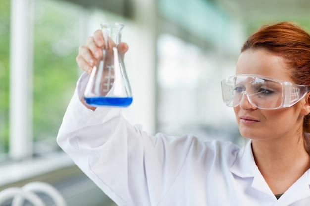 Estudante de ciências que olha um frasco erlenmeyr