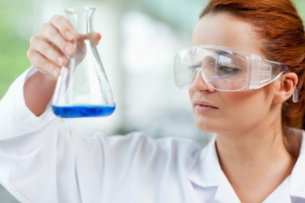 Estudante de ciências que olha um líquido