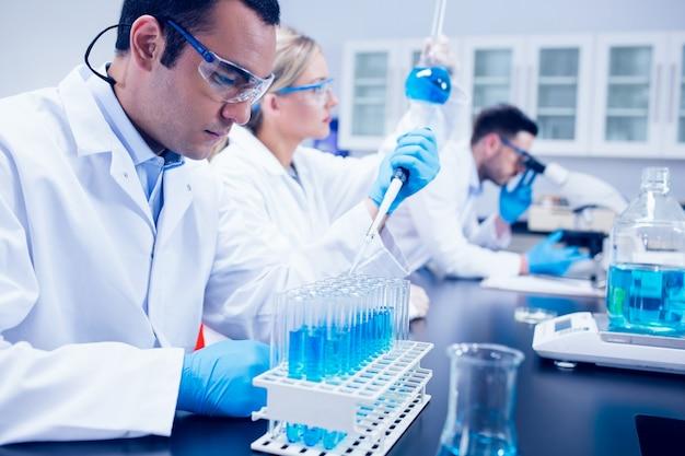 Estudante de ciências usando pipeta no laboratório para encher tubos de ensaio