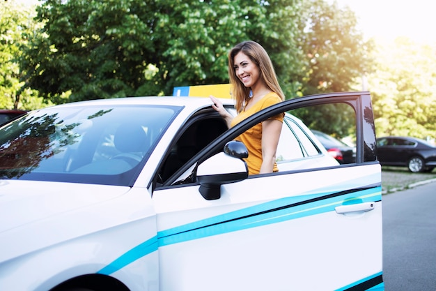 Estudante de condução de belo carro feminino entrando no veículo em sua primeira aula.