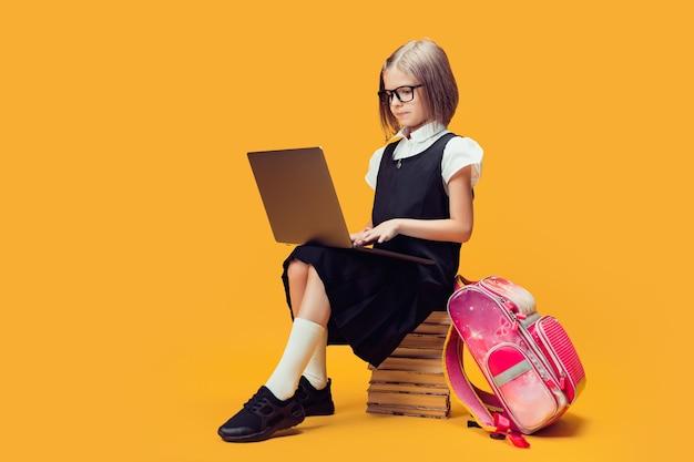 Estudante de corpo inteiro de uniforme sentada na pilha de livros, trabalhando no laptop, crianças, conceito de educação