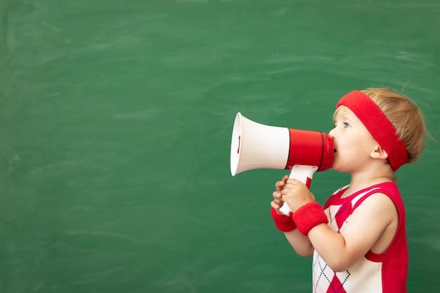 Estudante de criança engraçada falando por megafone em classe gritando pelo alto-falante contra a lousa verde.