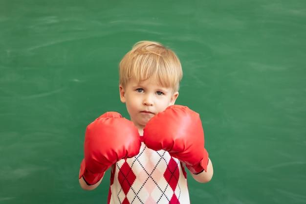 Estudante de criança engraçada usando luvas de boxe vermelhas na aula contra a lousa verde. educação física.