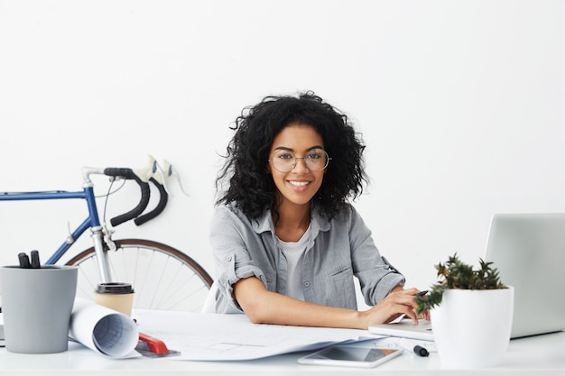 Estudante de design sorridente, sentada em seu local de trabalho, cercada de dispositivos