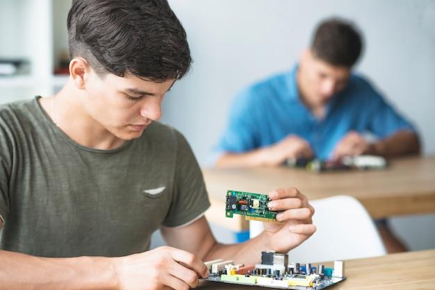 Estudante de engenheiro aprendendo a corrigir componente eletrônico na placa-mãe do computador